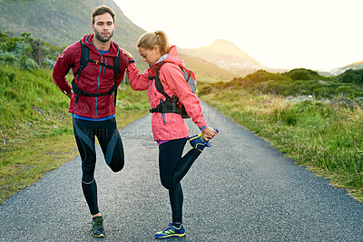 Buy stock photo Full length shot of a young couple warming up before their morning run