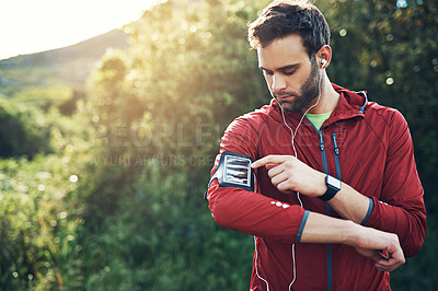 Buy stock photo Cropped shot of a handsome young male athlete preparing his playlist while out for a morning run