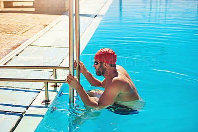 Buy stock photo Cropped shot of a handsome young male swimmer using the ladder to climb out of the swimming pool