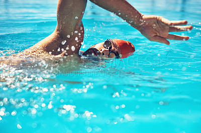 Buy stock photo Cropped shot of a handsome young male swimmer doing laps in a swimming pool