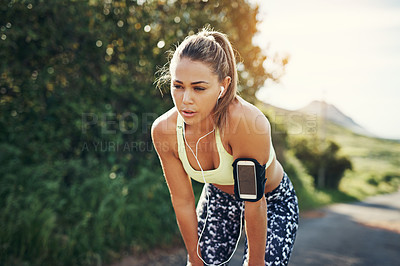 Buy stock photo Cropped shot of an attractive young female athlete looking tired during her morning run