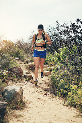 Buy stock photo Low angle shot of an attractive young female athlete out for a morning run