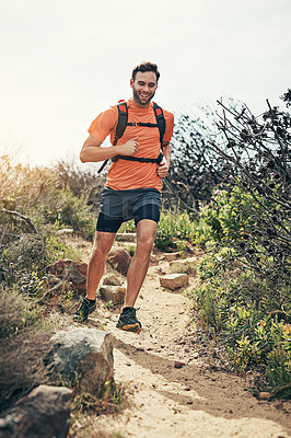 Buy stock photo Low angle shot of a handsome young male athlete out for a morning run