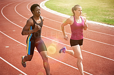 Buy stock photo Shot of two young athletes racing on the track