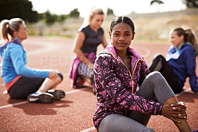 Buy stock photo Shot of a young woman sitting on the track with fellow athletes sitting in the background