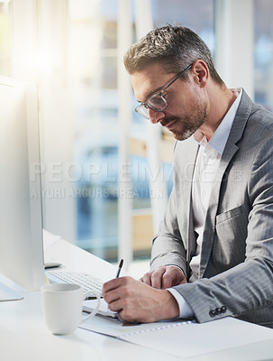 Buy stock photo Shot of a mature businessman writing notes while working on a computer in an office