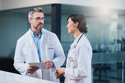 Buy stock photo Shot of two doctors working together on a digital tablet in a hospital