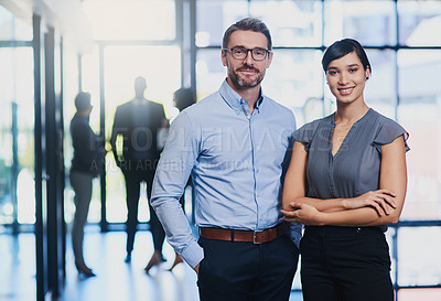 Buy stock photo Portrait of two businesspeople standing in an office with their colleagues in the background