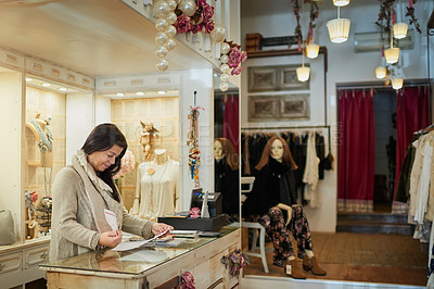 Buy stock photo Cropped shot of an attractive mature female entrepreneur reading a document while working in her self-owned boutique