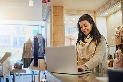 Buy stock photo Cropped shot of an attractive mature female entrepreneur working on a laptop in her self-owned boutique