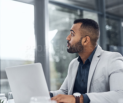 Buy stock photo Shot of a young businessman using a laptop and looking thoughtful in a modern office
