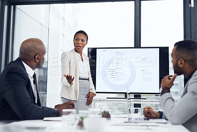 Buy stock photo Shot of a businesswoman delivering a presentation to her colleagues in the boardroom of a modern office