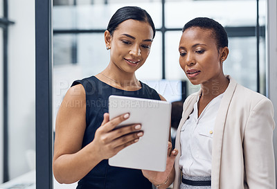 Buy stock photo Shot of two businesswomen using a digital tablet together in a modern office
