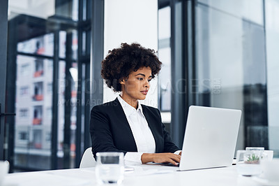 Buy stock photo Shot of a young businesswoman using a laptop at a table in a modern office