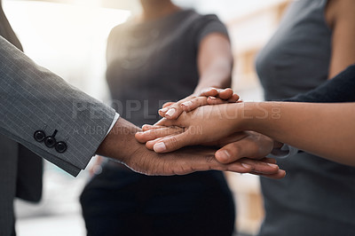 Buy stock photo Cropped shot of a team of colleagues joining their hands together in solidarity