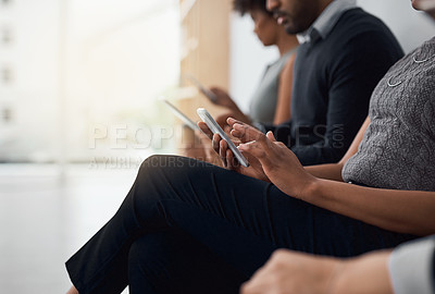 Buy stock photo Cropped shot of unrecognizable businesspeople using wireless devices while waiting in line