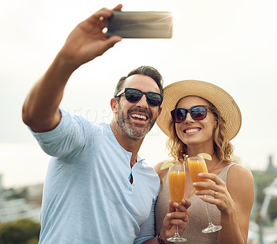 Buy stock photo Cropped shot of an affectionate mature couple taking selfies while drinking juice outside