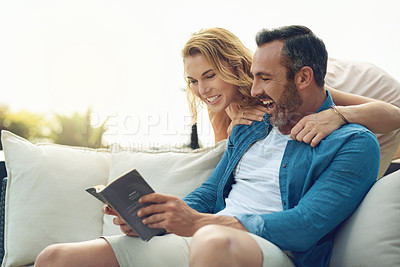 Buy stock photo Cropped shot of an attractive mature woman checking in with her husband while he sits outdoors reading a book