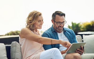 Buy stock photo Cropped shot of an affectionate mature couple using a tablet while sitting outside