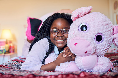 Buy stock photo Portrait of an adorable little girl holding a plush toy while lying on her bed in her bedroom
