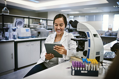Buy stock photo Shot of a young woman using a digital tablet while working in a laboratory