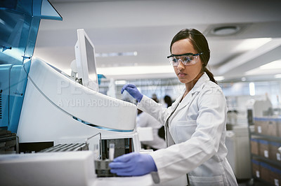 Buy stock photo Shot of a young woman using a machine to conduct a medical test in a laboratory