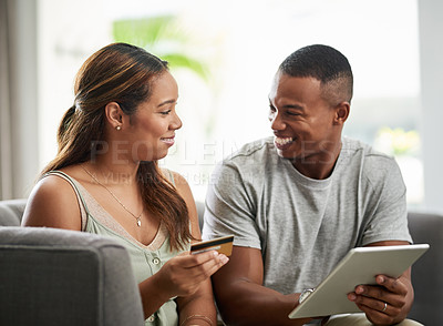 Buy stock photo Cropped shot of an affectionate young couple shopping online using their digital tablet