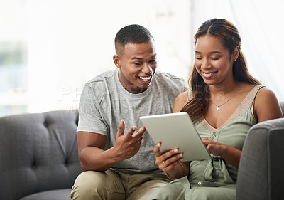 Buy stock photo Cropped shot of an affectionate young couple using their digital tablet while sitting on the sofa