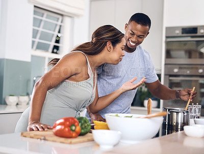 Buy stock photo Shot of a young couple cooking together at home