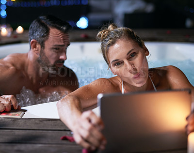 Buy stock photo Cropped shot of an affectionate mature couple taking selfies on their tablet while relaxing in a hot tub