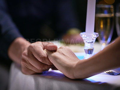 Buy stock photo Cropped shot of an unrecognizable affectionate couple holding hands while sitting at a dinner table