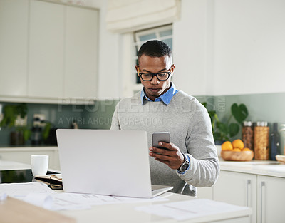 Buy stock photo Shot of a young man using a cellphone and laptop at home