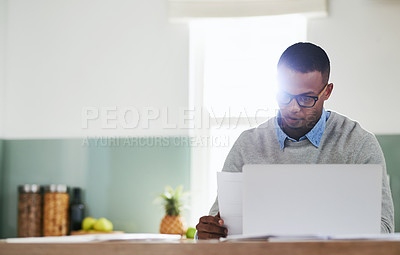 Buy stock photo Shot of a young man going through some paperwork while working on a laptop at home