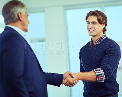 Buy stock photo Shot of two businessmen shaking hands in a modern office