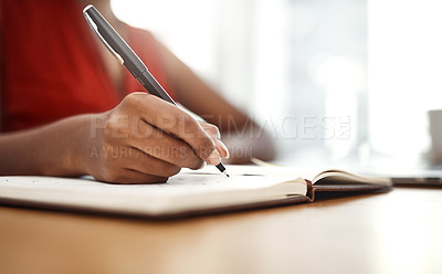 Buy stock photo Cropped shot of an unrecognizable businesswoman writing down notes in her notebook in her home office