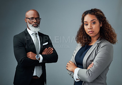 Buy stock photo Studio portrait of two corporate businesspeople standing with their arms crossed against a grey background
