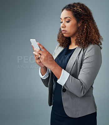 Buy stock photo Studio shot of a young businesswoman using a cellphone against a grey background