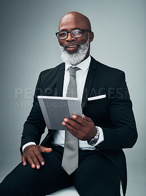 Buy stock photo Studio portrait of a mature businessman using a digital tablet against a grey background