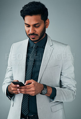 Buy stock photo Studio shot of a young businessman using a cellphone against a grey background