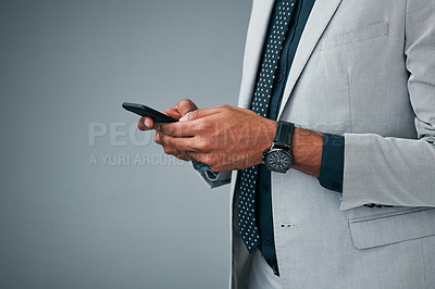 Buy stock photo Closeup shot of an unrecognizable businessman using a cellphone against a grey background