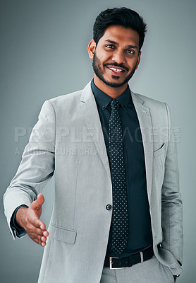Buy stock photo Studio portrait of a young businessman extending a handshake against a grey background