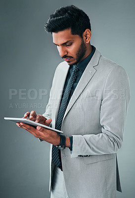 Buy stock photo Studio shot of a young businessman using a digital tablet against a grey background