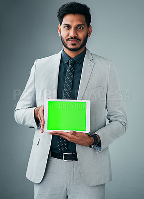 Buy stock photo Studio portrait of a young businessman holding up a digital tablet with a green screen against a grey background