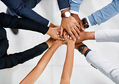 Buy stock photo High angle shot of a group of unrecognizable businesspeople standing with their hands in a huddle in the office lobby