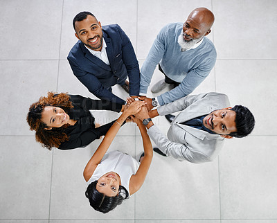 Buy stock photo High angle portrait of a group of businesspeople standing with their hands in a huddle in the office lobby