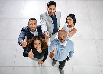 Buy stock photo High angle portrait of a group of businesspeople giving thumbs up while standing in their office lobby
