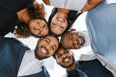 Buy stock photo Low angle portrait of a group of businesspeople standing in a huddle in their office