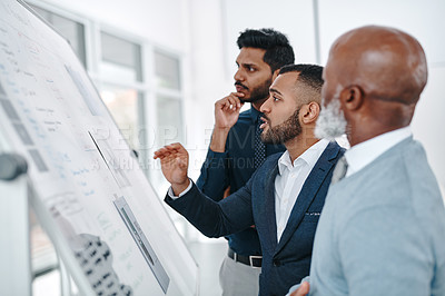 Buy stock photo Shot of three businessmen brainstorming together on a whiteboard in an office