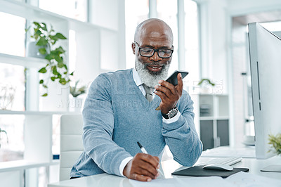 Buy stock photo Shot of a mature businessman talking on a cellphone while writing notes in an office