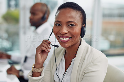 Buy stock photo Portrait of a call centre agent working in an office with her colleague in the background